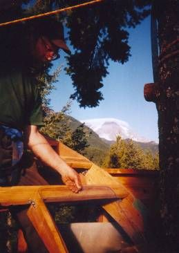Framing in a recycled car window in one of the arched roof sections.  (Note cloud cap over Mt. Rainier in background ...  indicates rain is on the way in a day or two.)